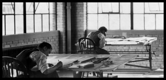 Old B&W photo of two man drafting